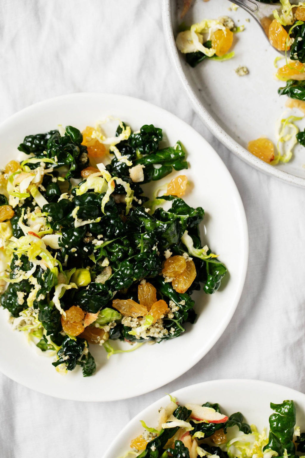A few serving plates of a wintery vegan Brussels sprout kale salad, topped with golden raisins.