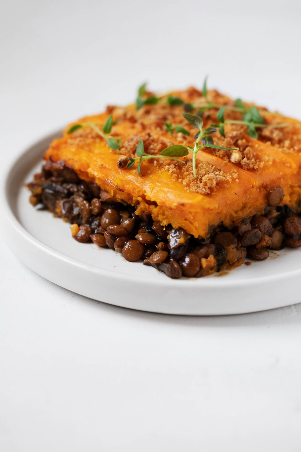 Sauteed lentils and mushrooms are baked with a sweet potato topping and cut into squares.