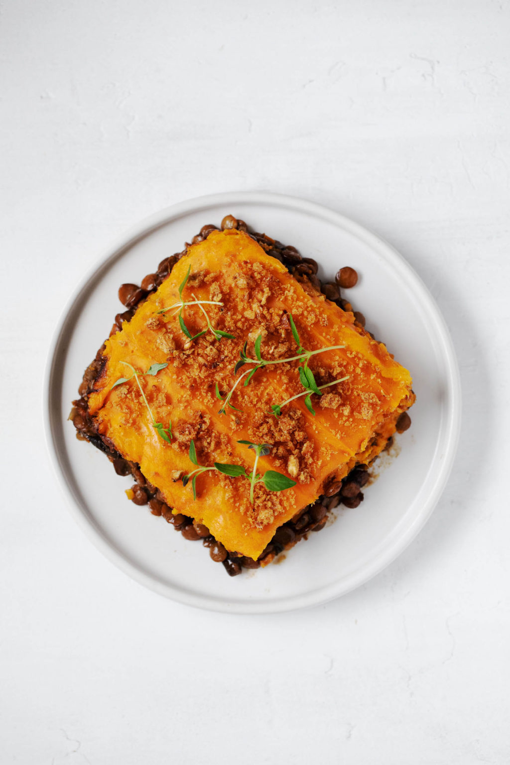 A neatly cut square of lentils, topped with mashed potatoes and garnished with herbs and bread crumbs.