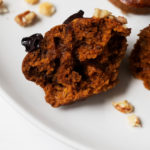 Half of a vegan pumpkin muffin with gingerbread spices, resting on a place with chopped walnut pieces.