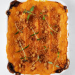 A small, rectangular baking dish is filled with a vegan sweet potato lentil shepherds pie.