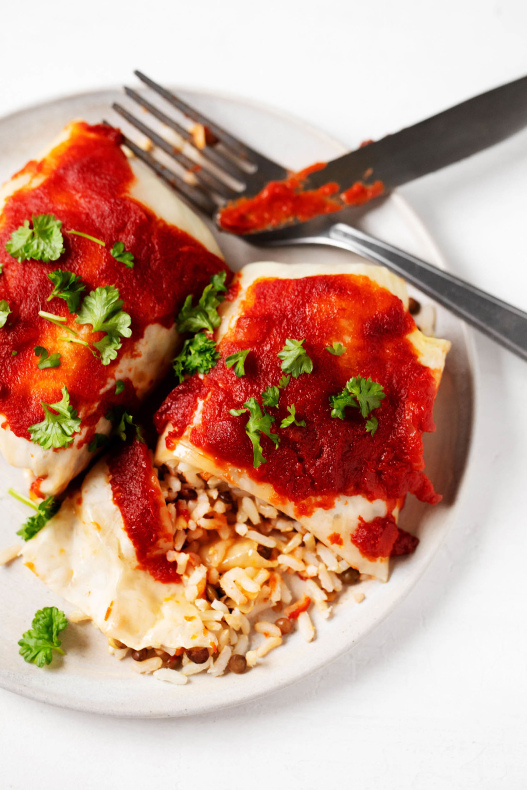 Two stuffed cabbage rolls, covered in tomato sauce, have been laid out on a plate and sliced into with a fork and knife.