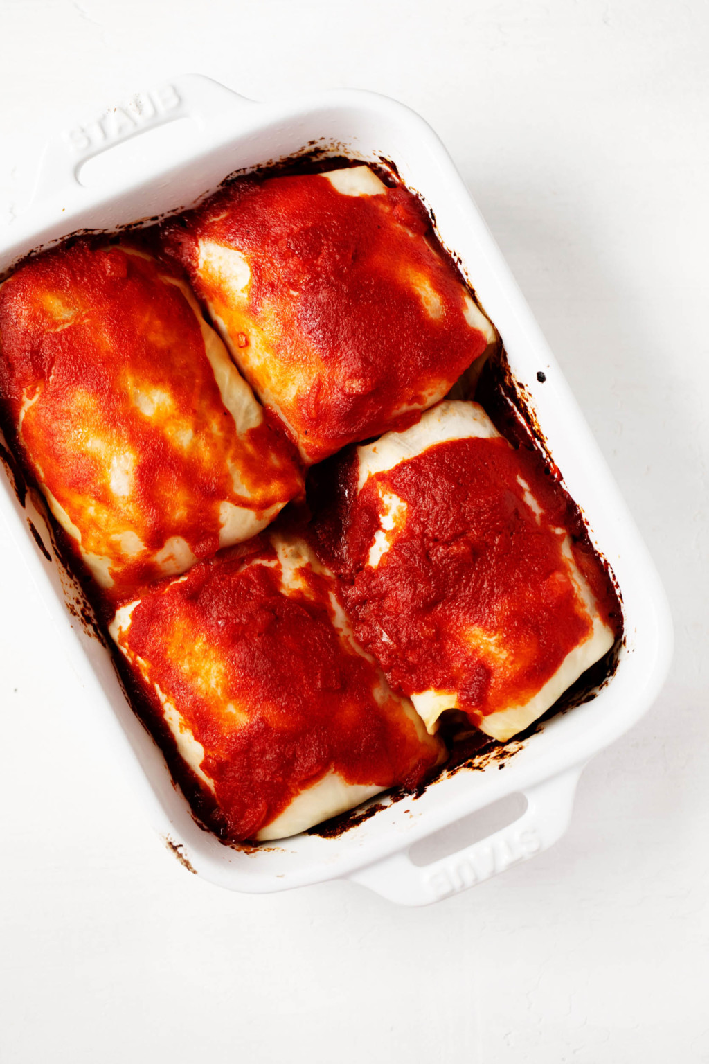 A small, rectangular, white baking dish has been filled with a plant-based entree.