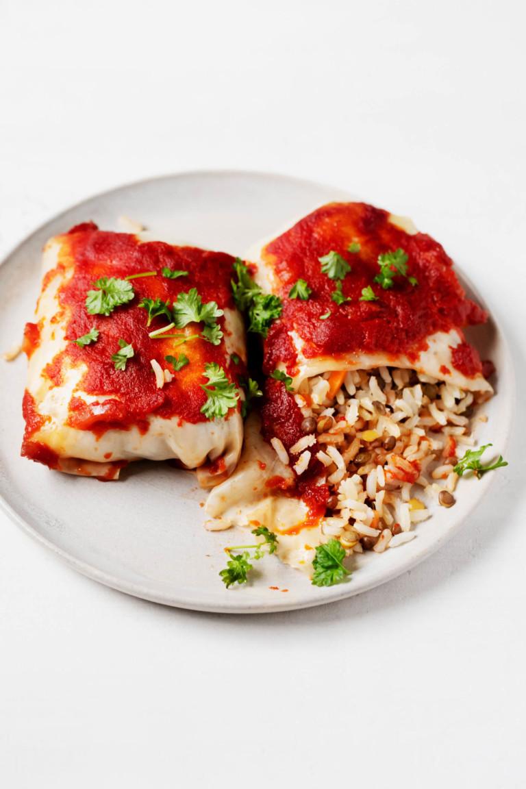 Two stuffed cabbage rolls are laid out, side by side, on a plate. One has been cut into and the filling is spilling out.