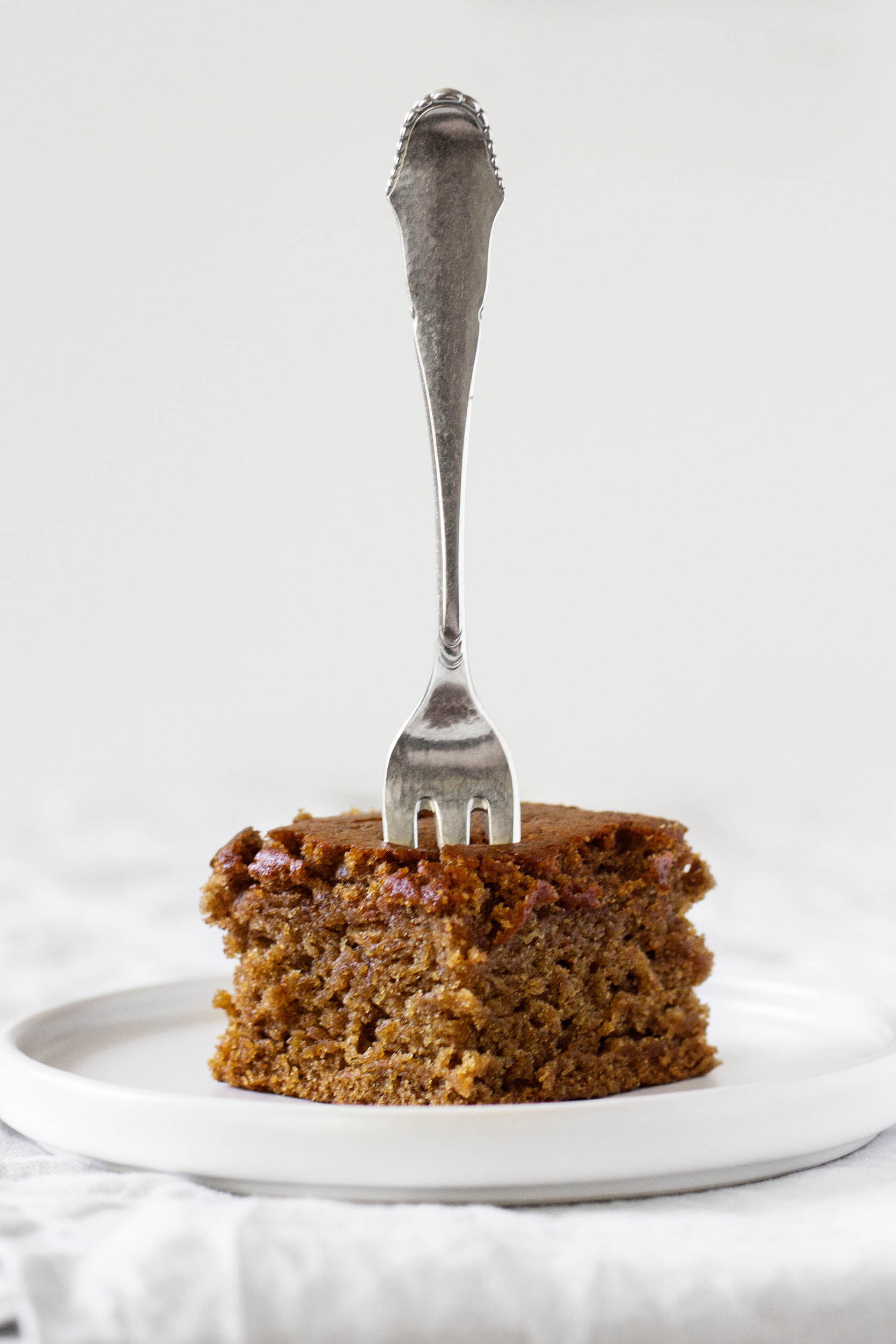 A slice of vegan gingerbread cake is pierced with a fork, ready to be eaten.