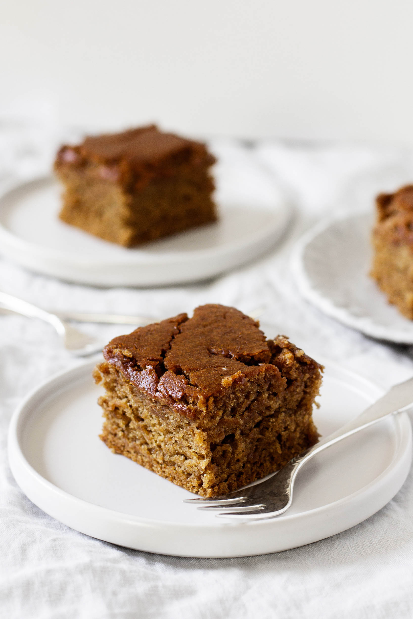 Several dessert plates are topped with squares of gingerbread and accompanied by dessert forks.