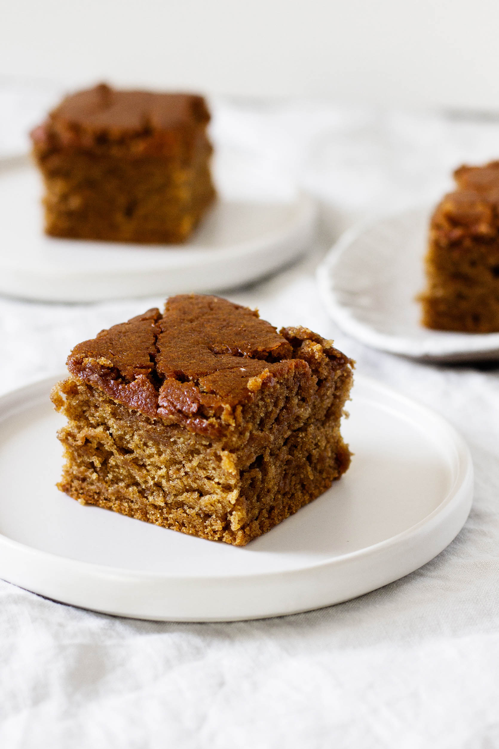 Dessert plates with square slices of vegan, gluten-free gingerbread cake.