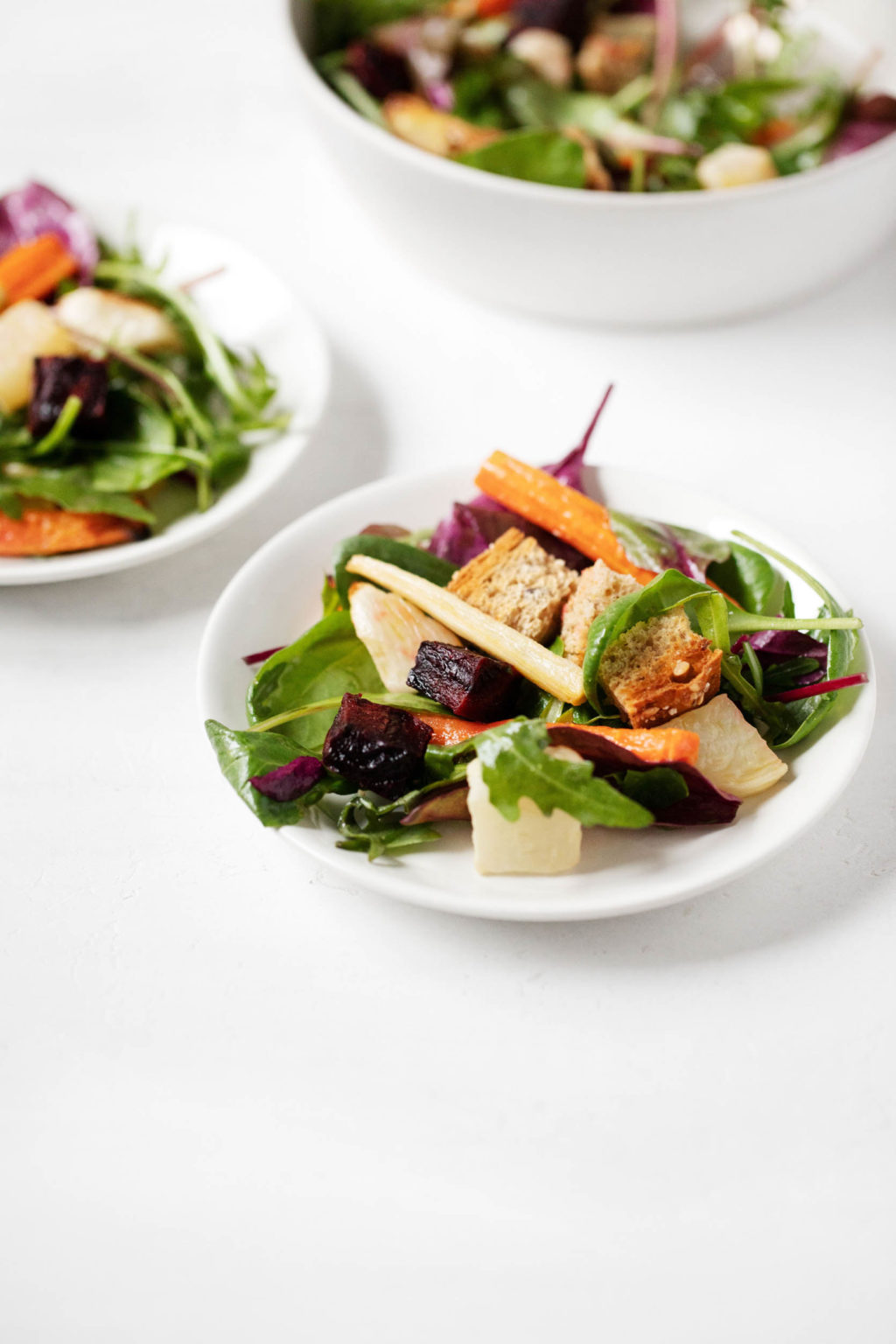An angled photo of small salad plates, topped with roasted root vegetables, greens, and cubed bread.