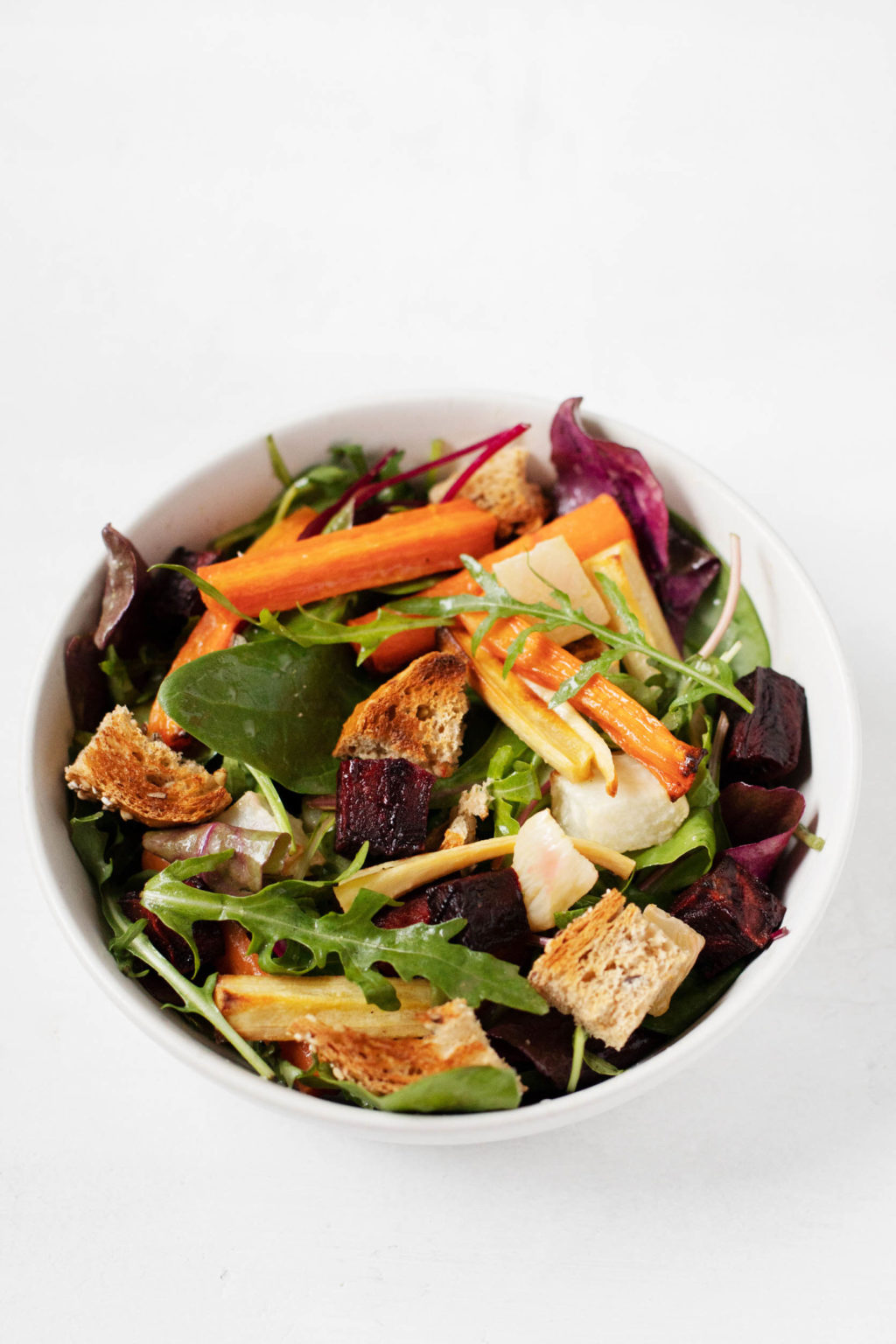 A round bowl, piled with the ingredients for a plant-based winter panzanella salad.