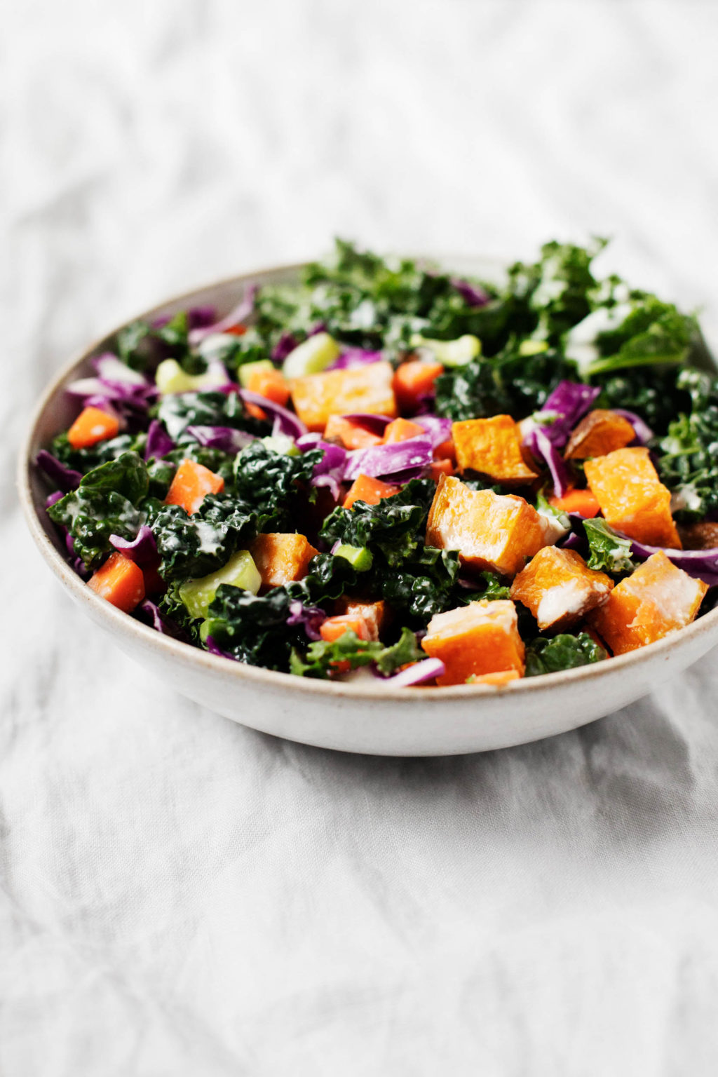 An angled photograph of a bowl of colorful winter greens and assorted vegetables.