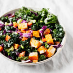 A serving bowl contains a colorful, plant-based kale salad.
