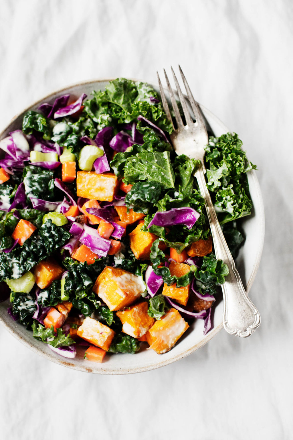 A vibrant bowl of vegetables has been topped with a creamy dressing. A fork accompanies the colorful meal.