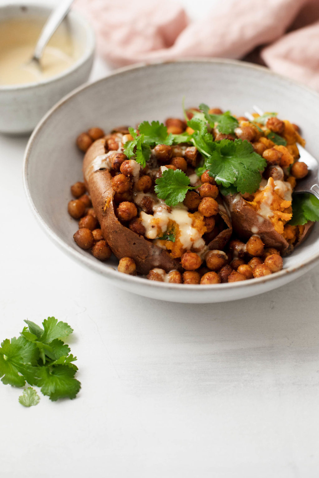 A small bowl holds a baked sweet potato that's been stuffed with spiced chickpeas, herbs, and sauce.