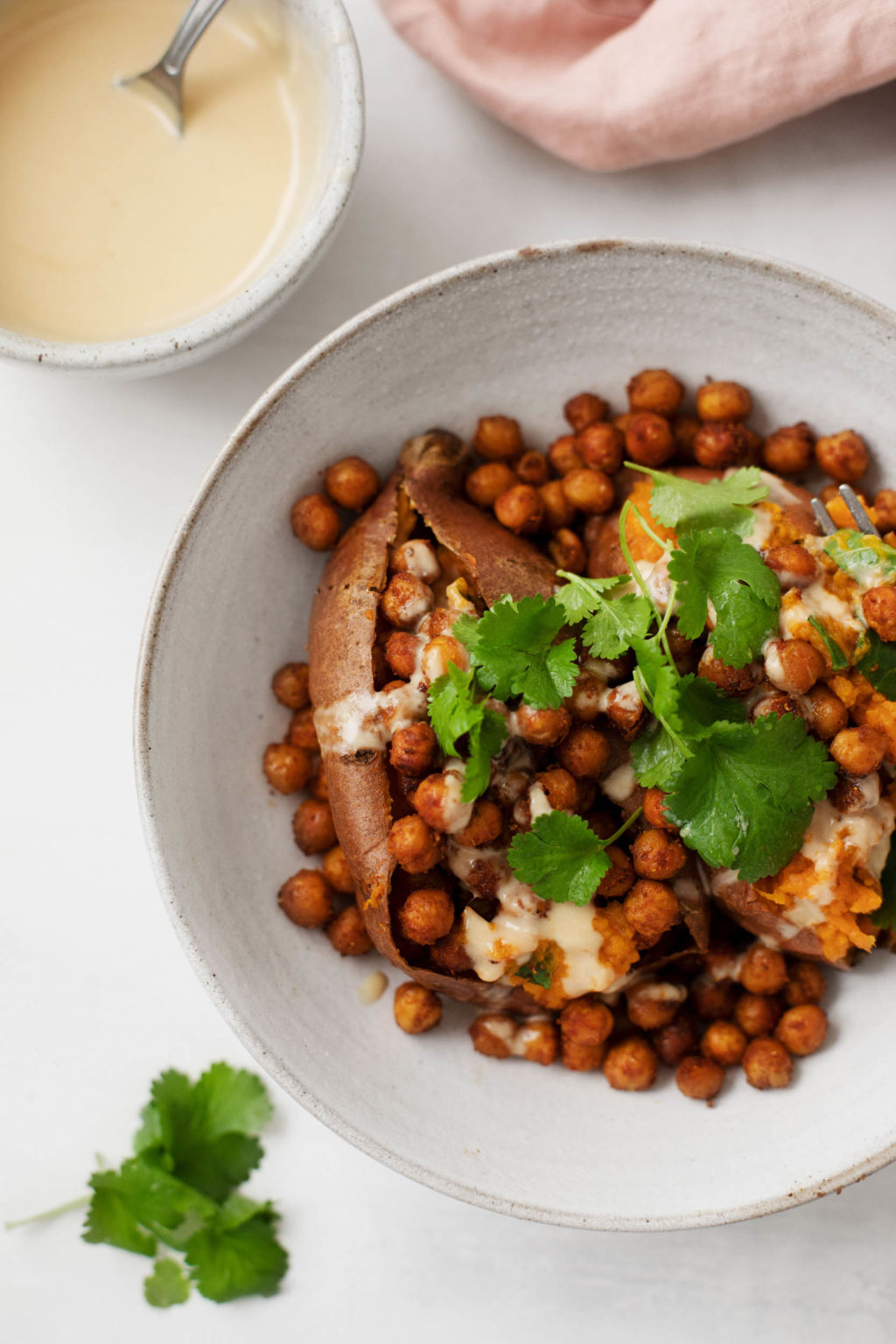 A zoomed in image of a Tandoori spiced sweet potato, stuffed with chickpeas, fresh cilantro, and a drizzle of tahini lime sauce.
