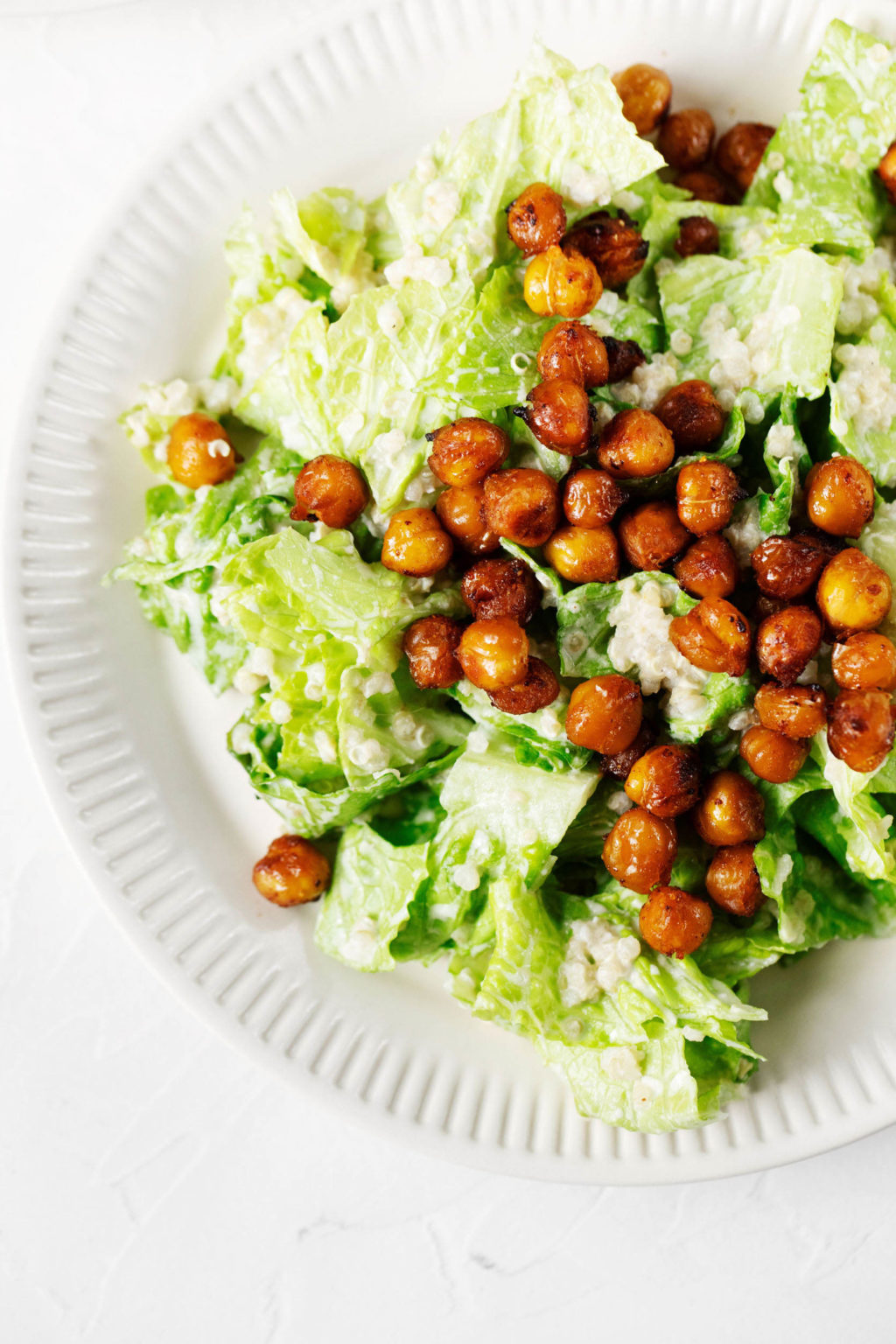 An overhead image of a white, fluted plate, which has been topped with vegan Caesar salad and roasted chickpeas.