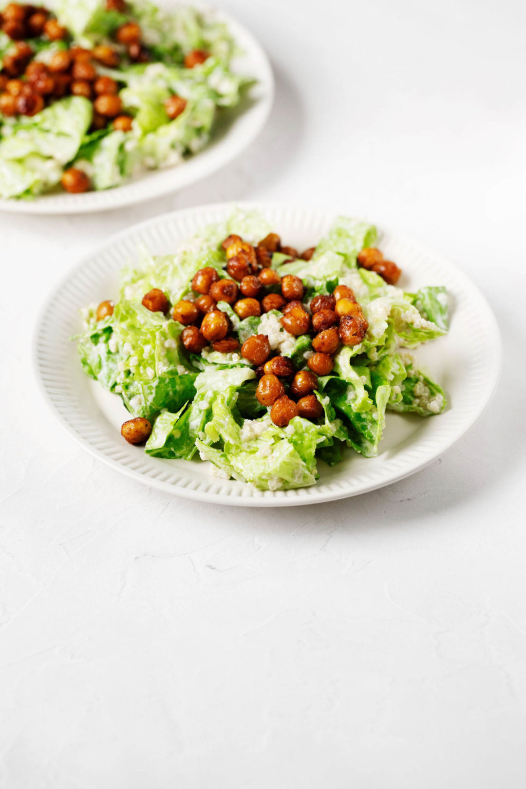 An angled photograph of a white surface, which is topped with two fluted white plates that are holding vegan quinoa chickpea Caesar salad.