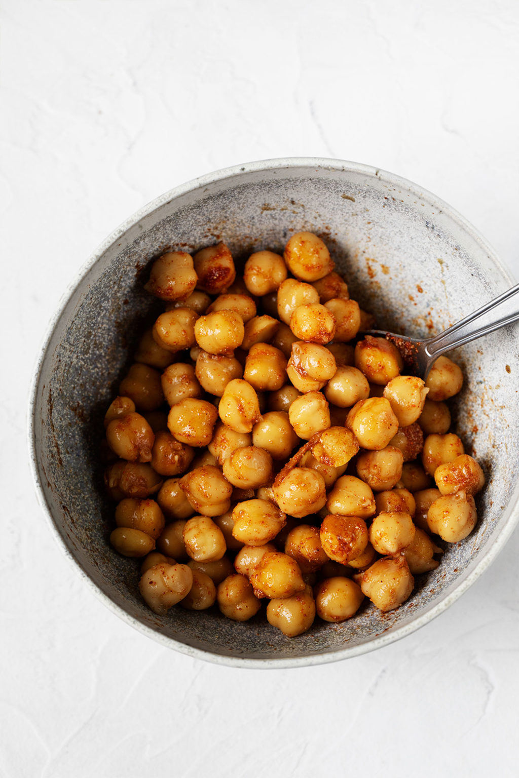 A small, white and gray ceramic bowl holds chickpeas that are being tossed with olive oil and spices.
