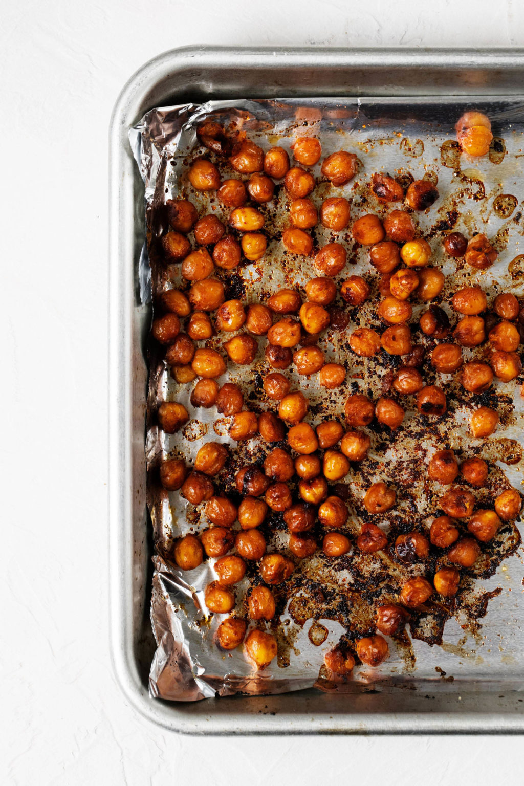 A silver baking sheet is lined with foil and filled with crispy roasted chickpeas.