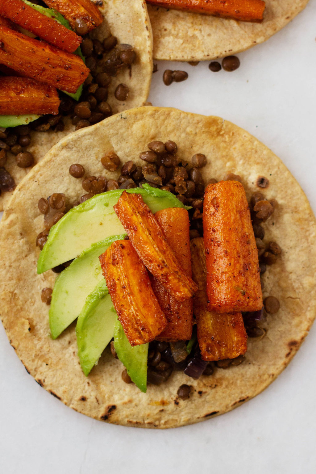 A close up, overhead shot of plant-based tacos with roasted carrots, avocado slices, and spiced lentils.