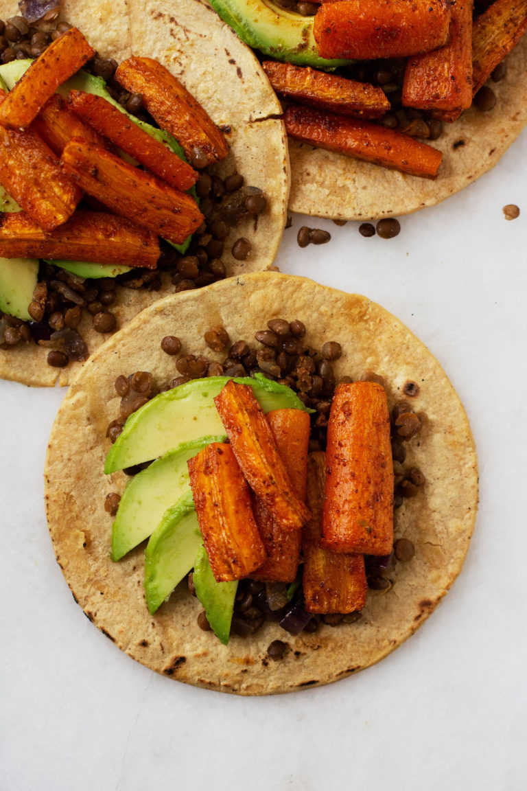 Three vegan roasted carrot lentil tacos with avocado slices.