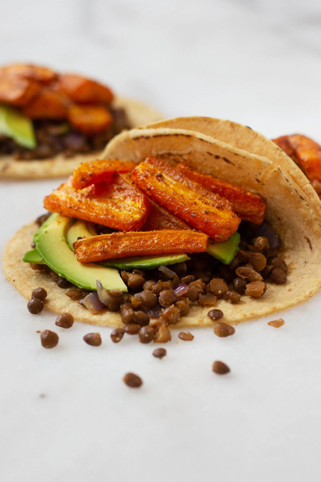 An angled shot of open, vegan tacos with a carrot and lentil filling, spilling onto a marble surface.
