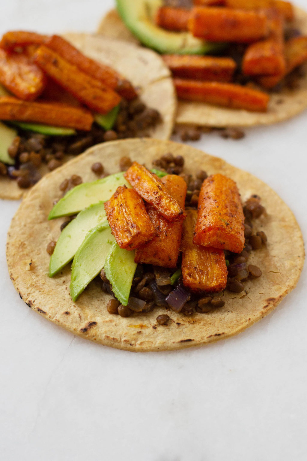Three vegan tacos, each filled with roasted carrots, a spiced lentil and onion mixture, and avocado slices.