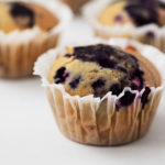 A few corn muffins, filled with juicy blueberries, are resting in muffin liners on a white surface.
