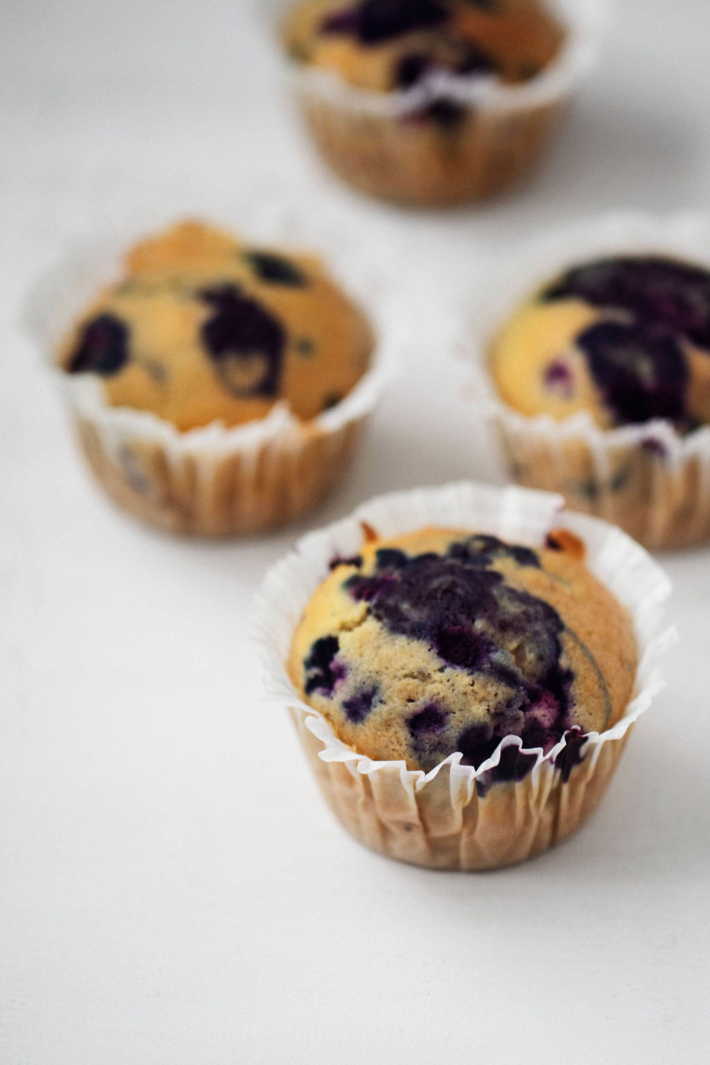 An angled photograph of vegan blueberry corn muffins, which are arranged on a white surface.