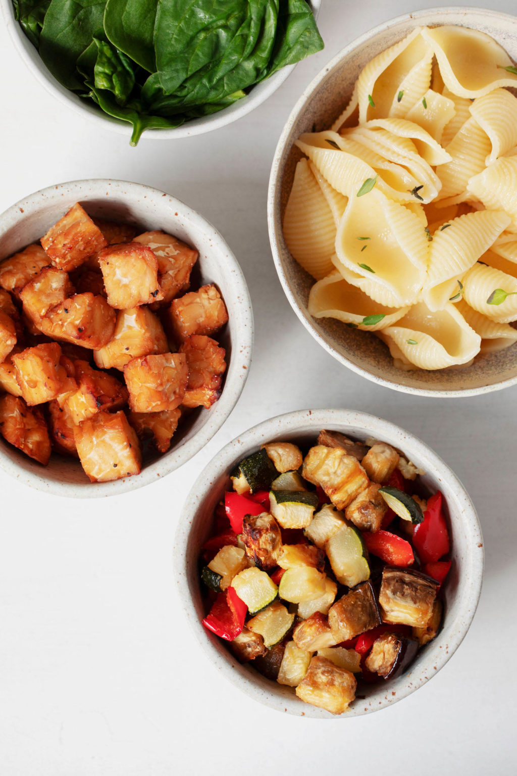 A few small, white bowls are filled with the ingredients needed to make a vegetable pasta salad.