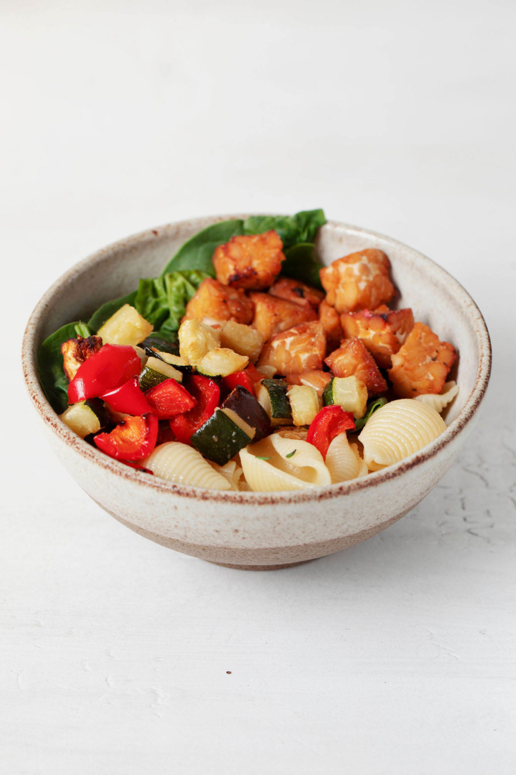 A small, white and beige bowl is resting on a white surface. The bowl is filled with cooked pasta and colorful mix-ins.
