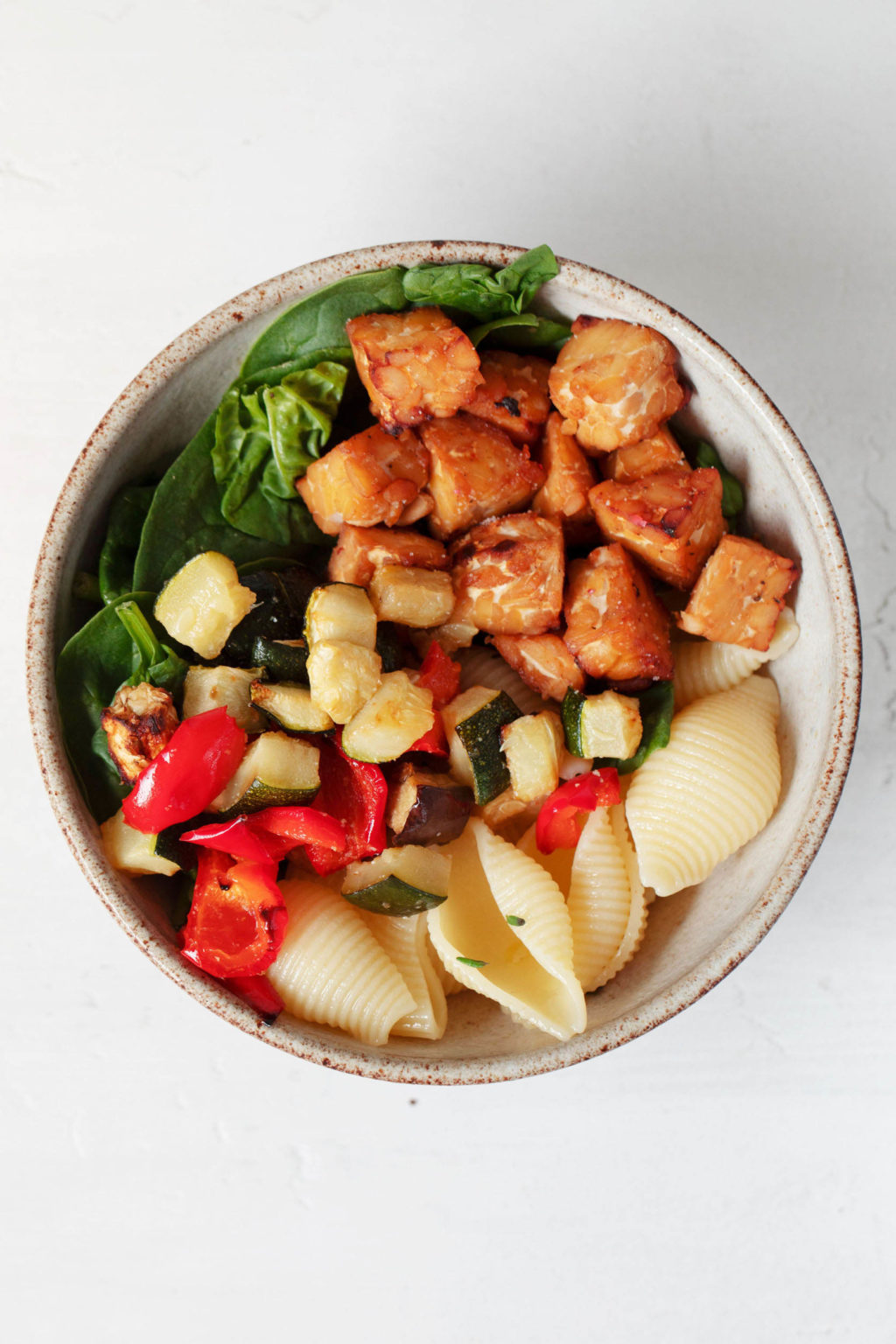 An overhead image of a serving dish that holds roasted tempeh cubes, spinach, and roasted vegetables. The colorful mixture is set against a white backdrop.