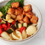 A round, white ceramic bowl has been filled with a colorful tempeh vegetable pasta dish. It rests on a white surface.