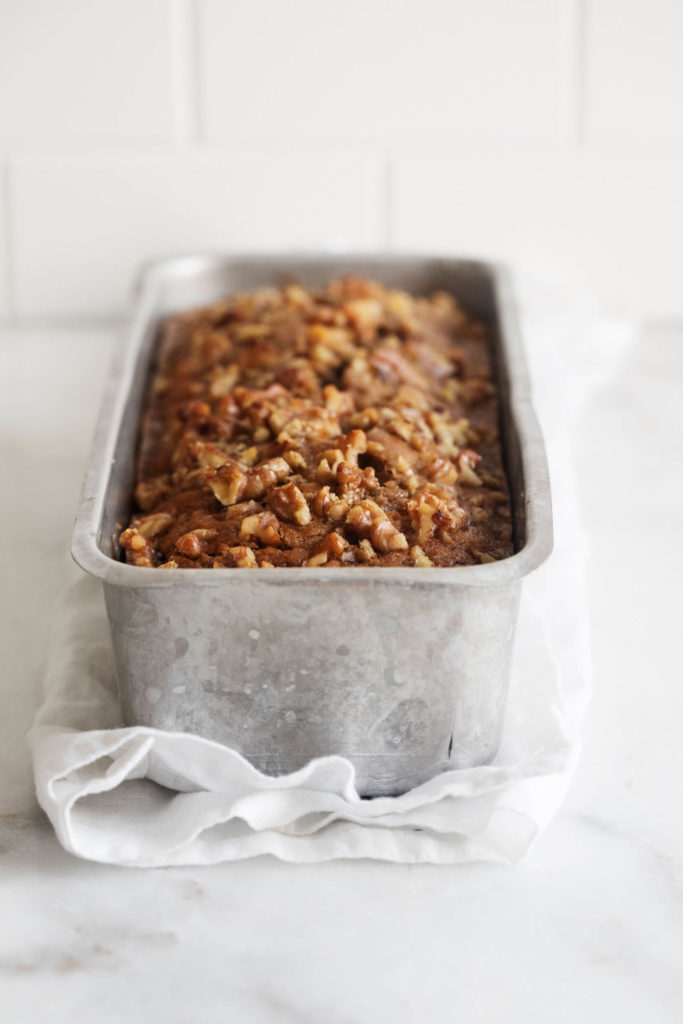 A silver loaf pan holding a freshly baked quick bread that's topped with chopped walnuts..