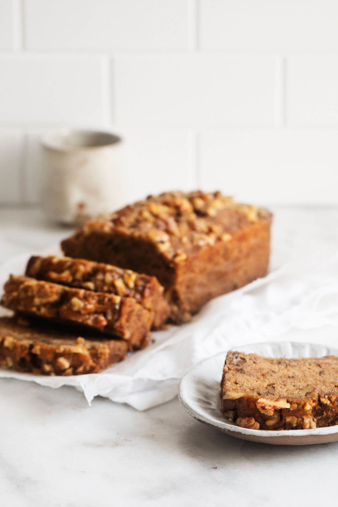 An angled photograph of classic vegan banana bread, sliced and ready to serve