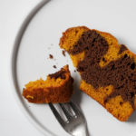 An overhead shot of a piece of pumpkin chocolate marble loaf on a serving plate, with a bite ready to be eaten.