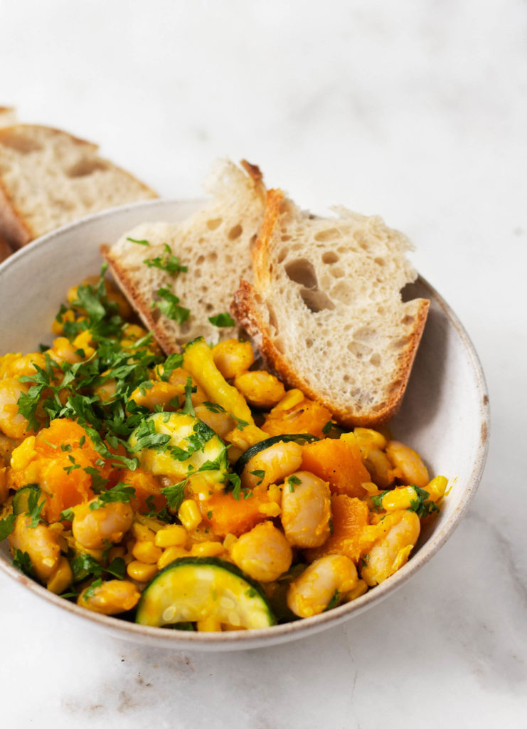 A close up shot of a dish of plant-based lima bean butternut succotash.