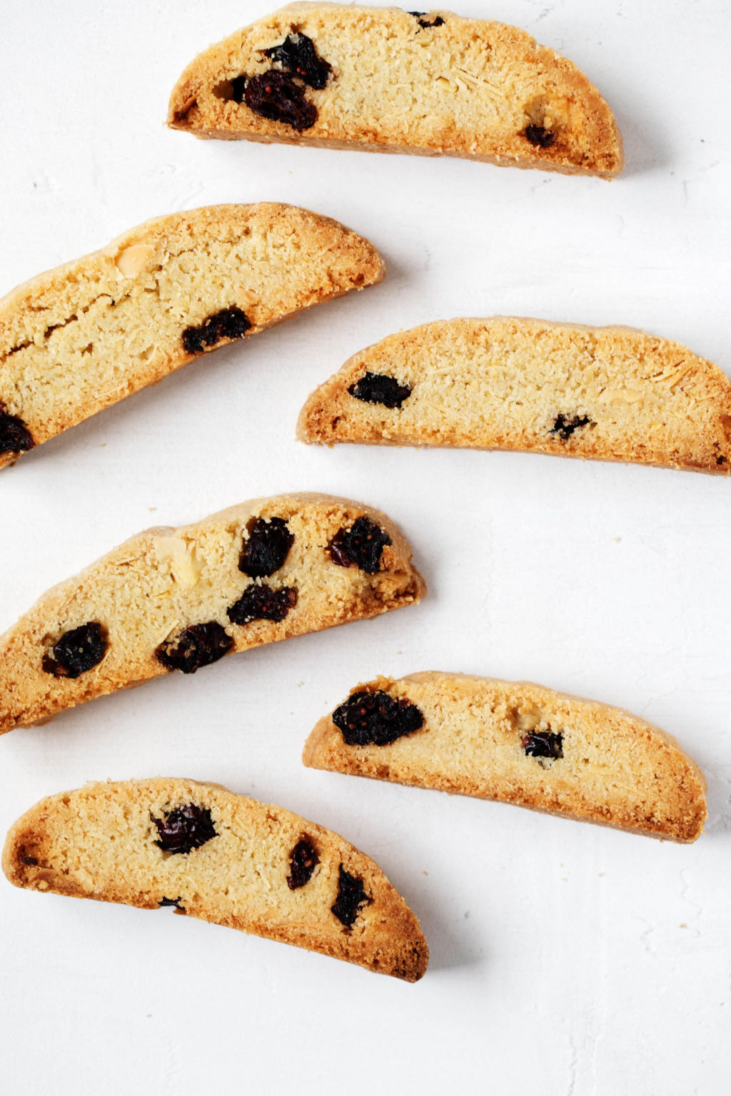 Cranberry almond biscotti cookies are laid out neatly on a white surface.