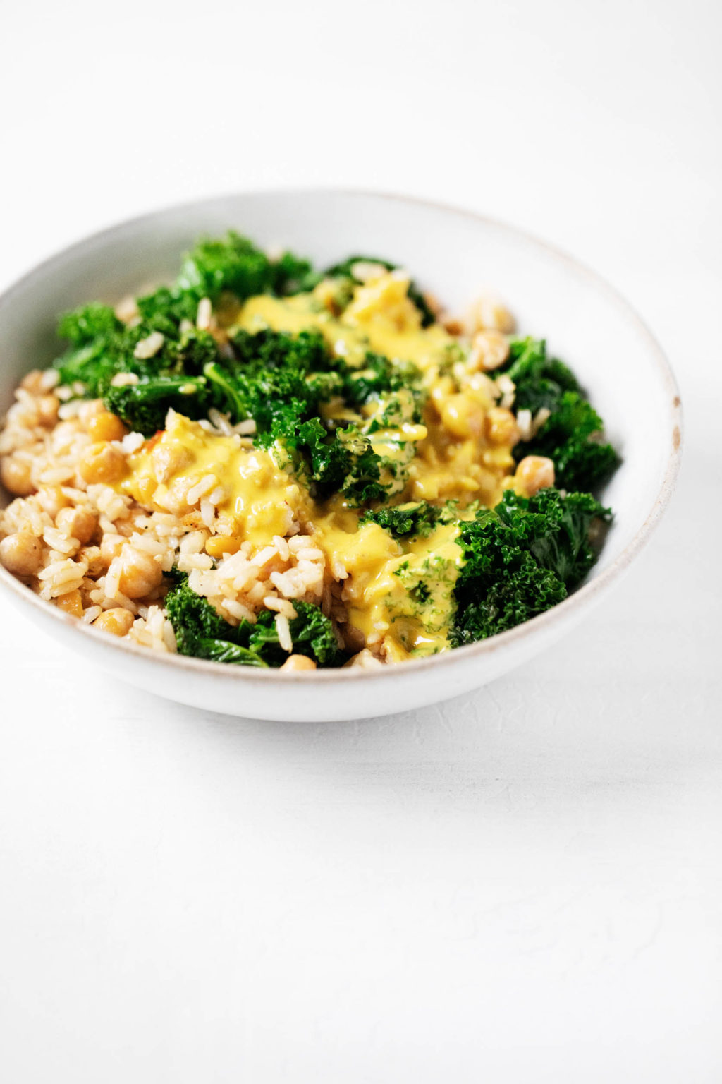 An angled photograph of a bowl of whole grains, beans, and greens, which have been dressed with a golden-hued, creamy sauce.