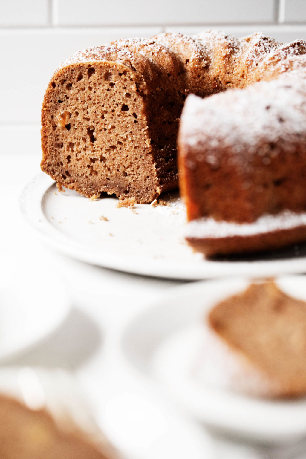 A large, white plate has been topped with a round applesauce spice bundt cake. A few slices of the cake peek out in the foreground.