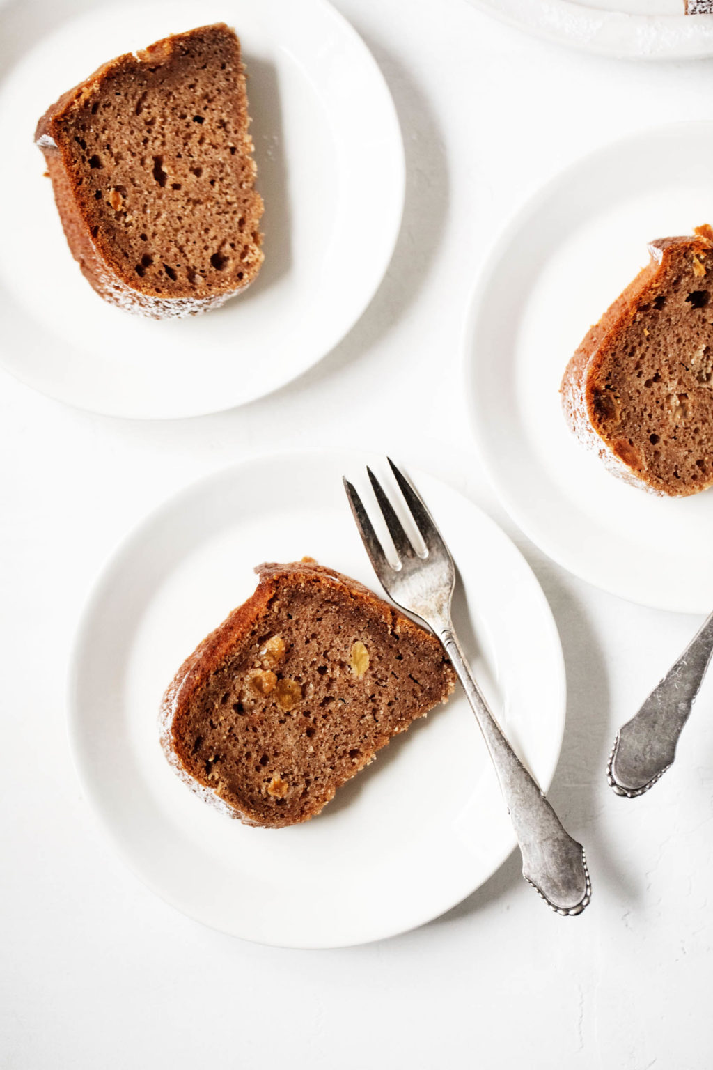A few small white dessert plates have been topped with slices of a bundt cake.