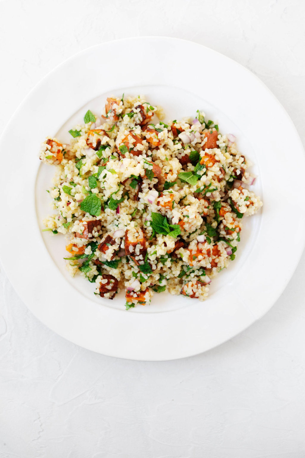 An overhead image of a wide, round plate against a white backdrop. The plate holds a vegan whole grain salad.