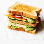 A colorful, three layered vegan green goddess sandwich is placed on a small piece of parchment paper, waiting to be cut in half.