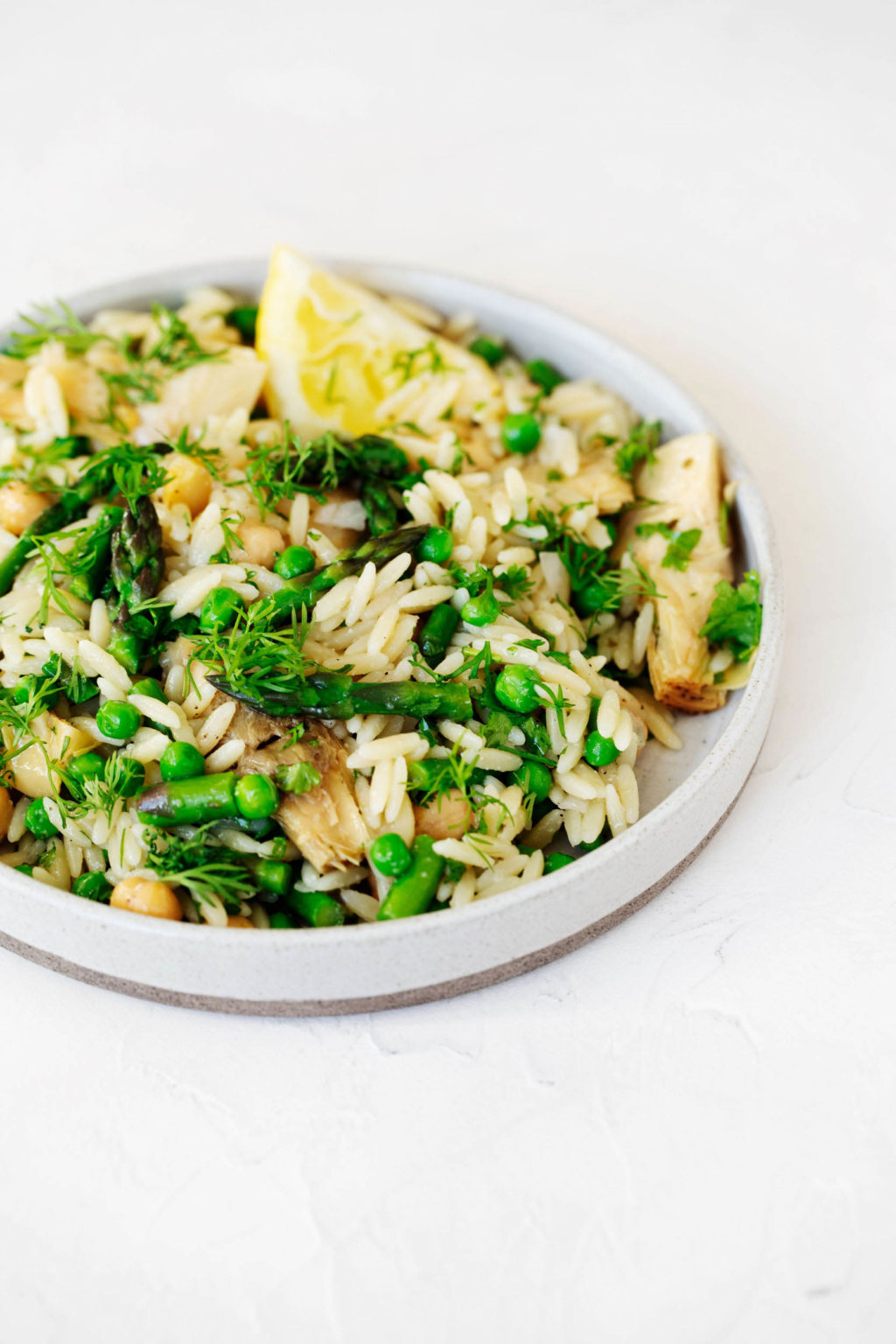 A rimmed, round white plate has been filled with an orzo pasta salad that's packed with vegetables and herbs. It rests on a white surface.