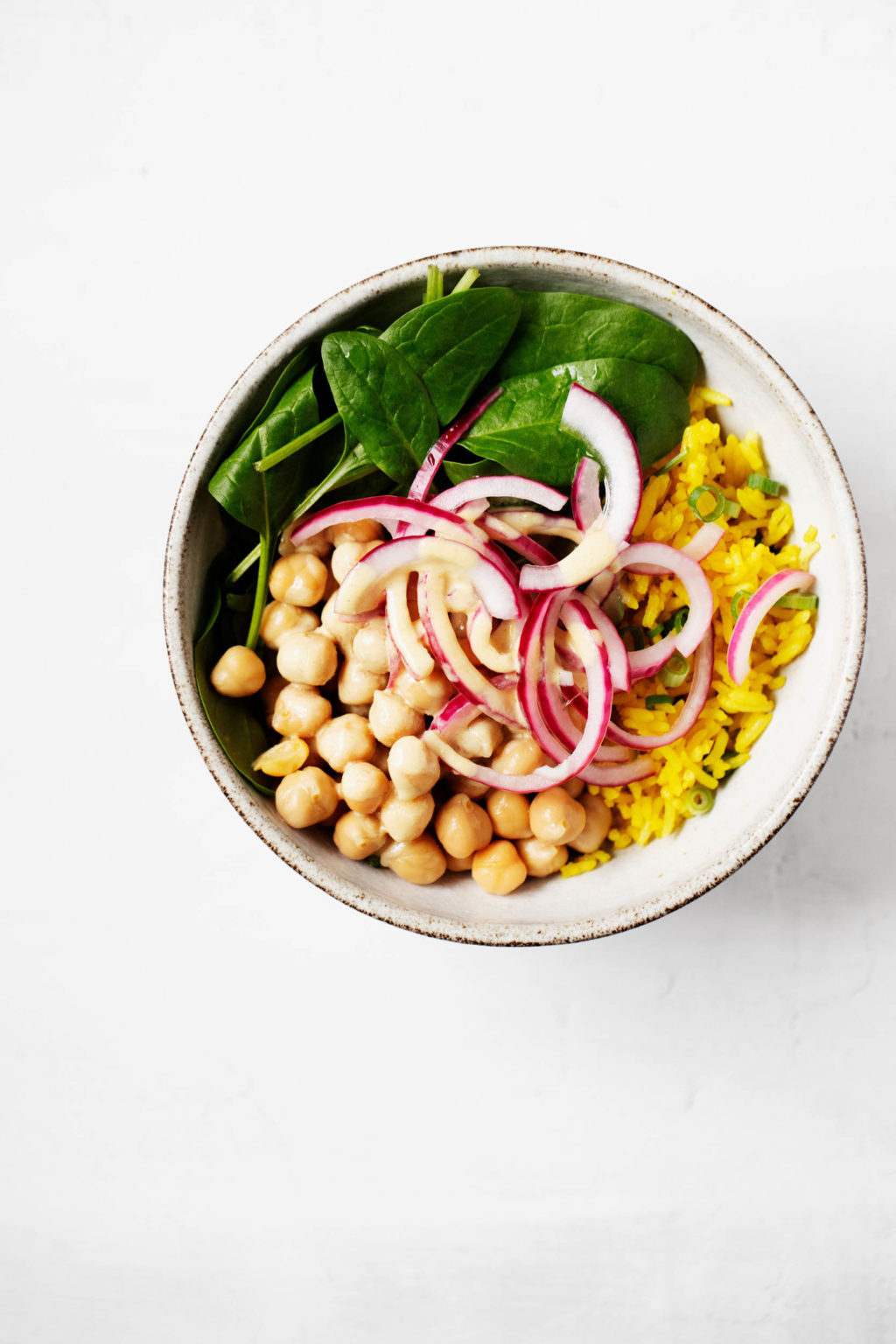A small white bowl has been filled with rice, chickpeas, and vegetables.