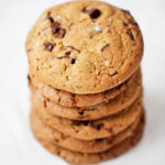 A stack of chewy, vegan chocolate chip cookies rests on a while sheet of parchment.