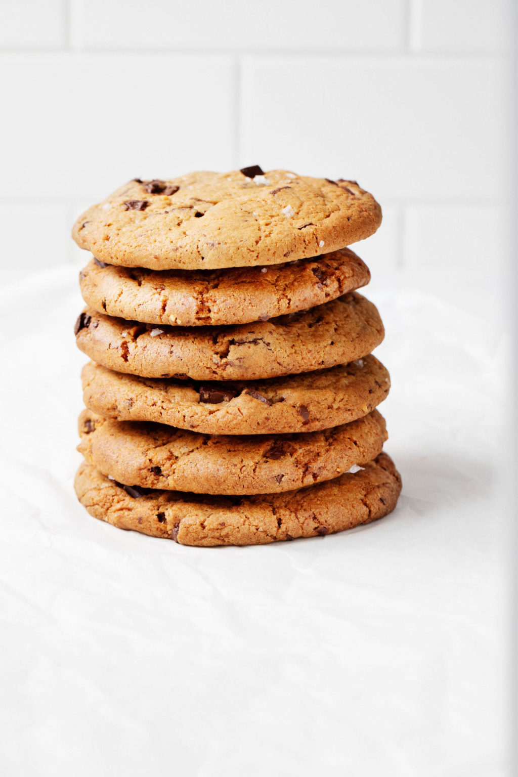 An angled photo of a stack of vegan cookies. It rests on a parchment paper sheet against a white backdrop.