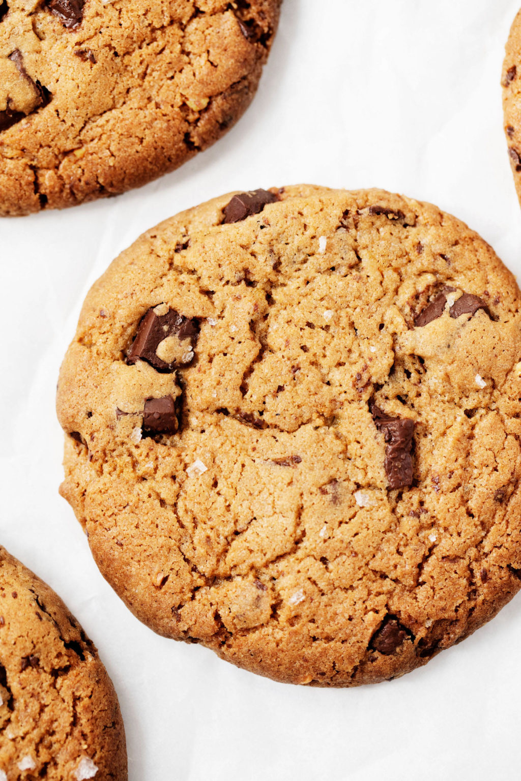 A close up, overhead photograph of vegan chocolate chip cookies placed on a white parchment surface.