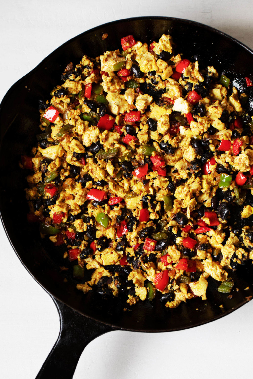 A black, cast iron skillet is filled with a mix of black beans, vegetables, and soy protein.