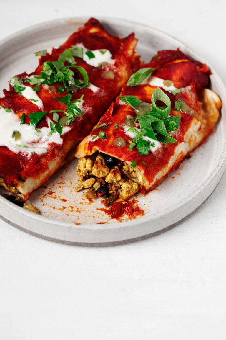 A white, rimmed plate holds two vegan enchiladas that have been filled with tofu scramble and black beans.