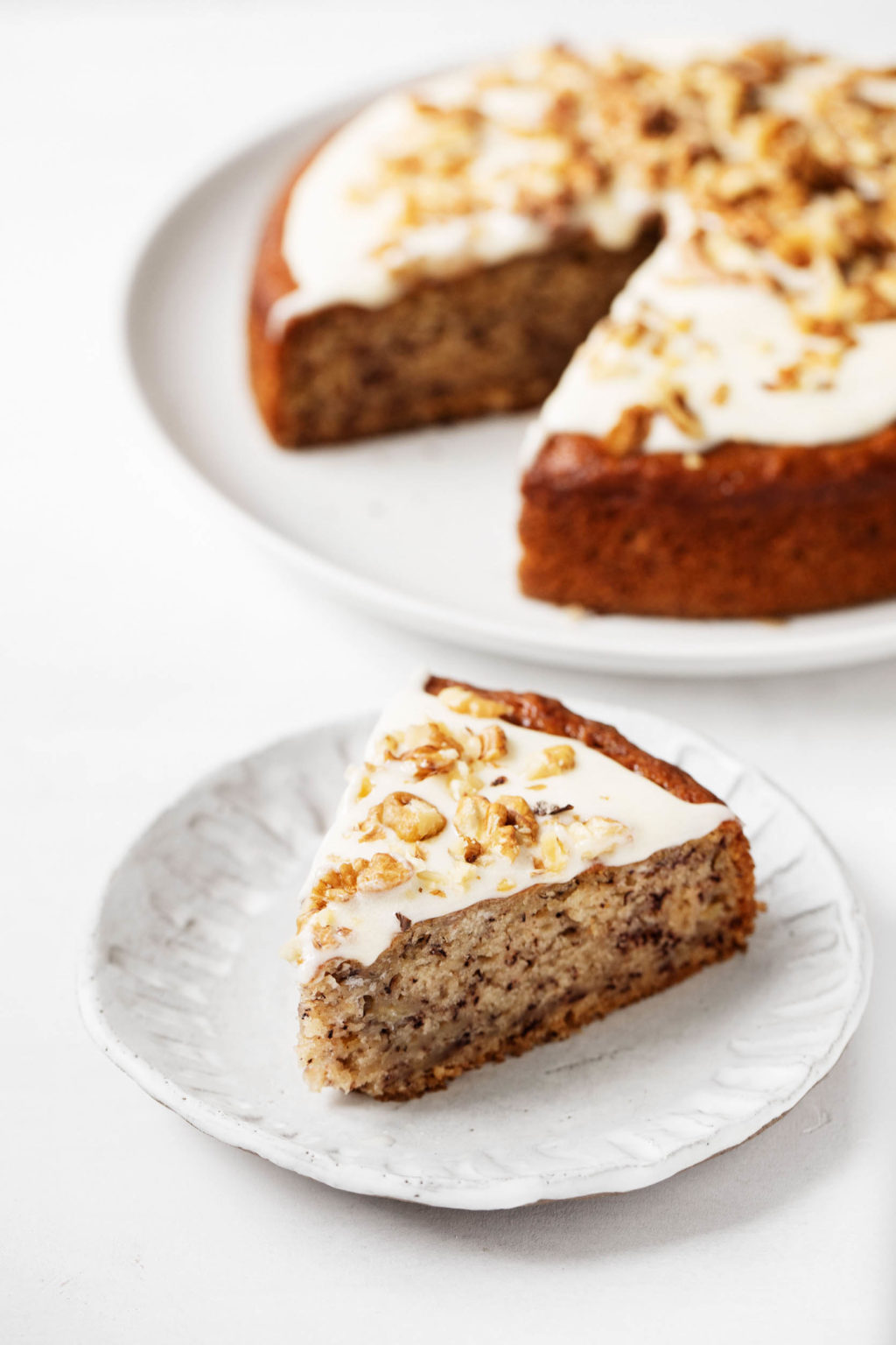 A beautiful, freshly cut slice of vegan banana cake rests on a small dessert plate, decorated with frosting and chopped nuts.